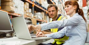 Man and woman using a laptop in warehouse